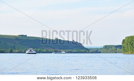 Barge Sailing On Rhine River Past Green Hills With Vineyards