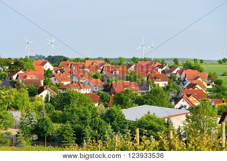 Aerial view of a small german village with red roofs and wind generators