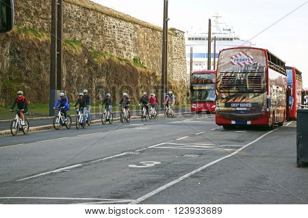 Oslo, Norway - May 08, 2013: bicyclists on the street of Oslo near the fortified wall and port