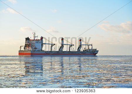 Cargo ship (bulk carrier) sailing in frozen winter sea