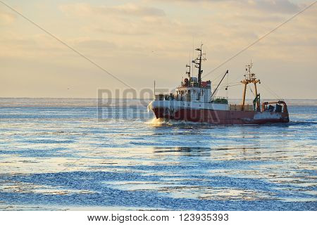 Frozen fishing vessel coming back to the port at sunset