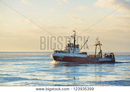 Frozen Fishing Vessel In Coming Back To The Port At The Sunset