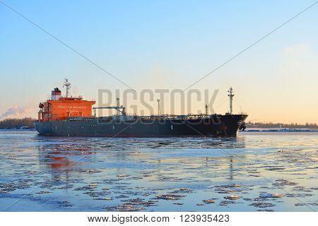Cargo ship (bulk carrier) sailing in still frozen sea