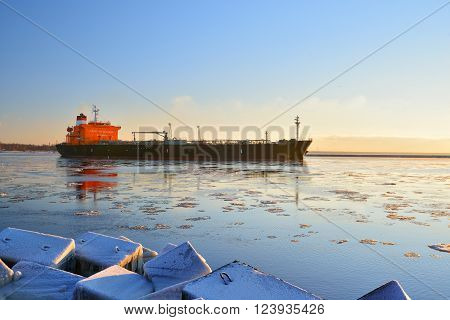 Cargo ship (bulk carrier) sailing in still frozen sea with snow-covered stones at the foreground