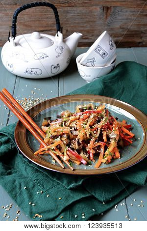 Asian salad with aubergines on the wooden background