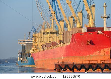 Big red cargo ship loading in a frozen winter port