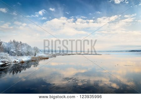 Beautiful winter lake landscape in Latvia. Blue sky with clouds reflecting in still water.