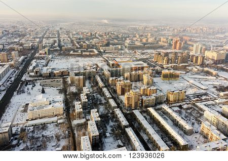 Tyumen, Russia - January 23, 2016: Aerial view on city quarters, city drama theater and square with big fir-tree and ice slopes