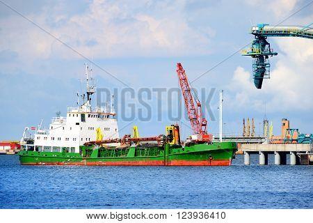 Green cargo tanker ship in industrial port