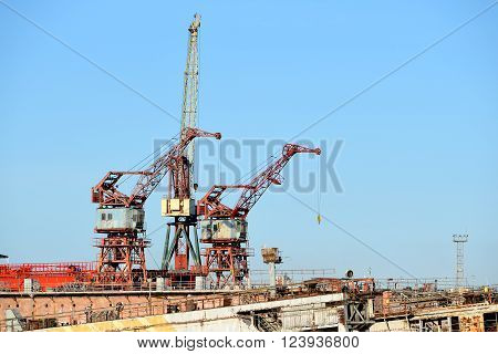 Port cargo cranes and ship fragment at the docks