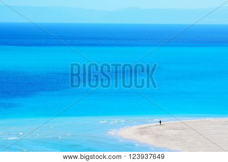 man fishing in a blue sea in Sardinia Italy