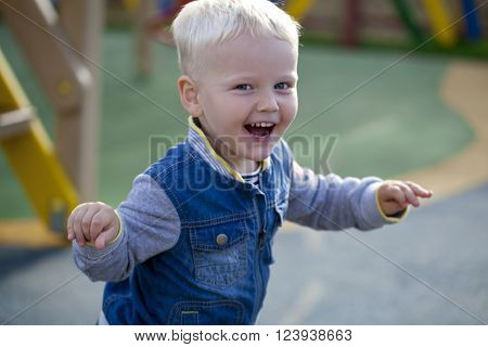Portrait of blonde baby boy in summer park