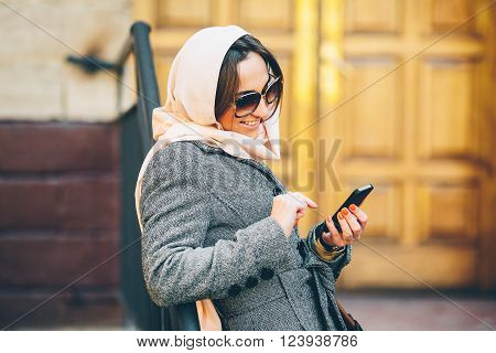 beautiful girl in a coat on the street sends sms ** Note: Visible grain at 100%, best at smaller sizes