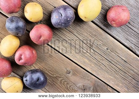 Corner border of colorful fresh little potatoes over a rustic old wooden background