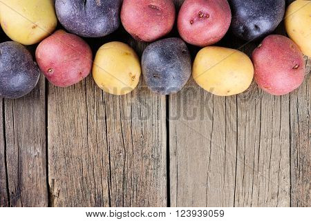 Top border of colorful fresh little potatoes over a rustic old wooden background