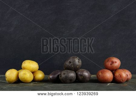 Three Piles Of Yellow, Purple And Red Fresh Little Potatoes Over A Dark Slate Background