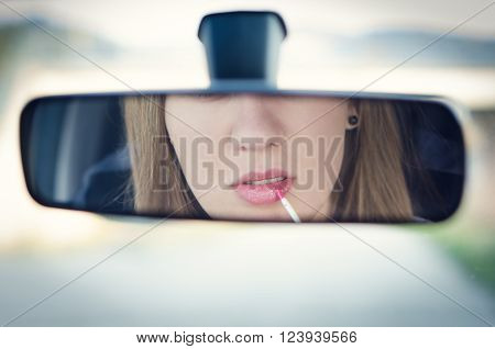 Woman putting make up in a car. Pretty young woman looking in mirror. Dangerous situation.