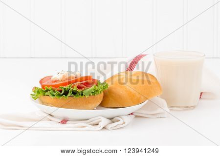 Tomato and ham sandwich on a fresh kaiser bun served with a glass of cold milk.