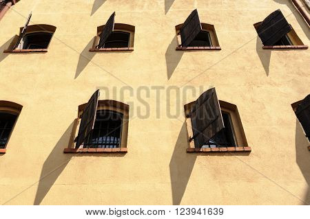TORUN POLAND - JULY 7 2009: Facade of medieval gothic granary with wooden shutters on windows
