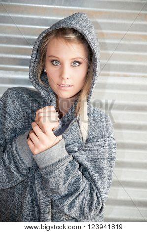Twenty something sportyfemale model wearing a hooded sweatshirt