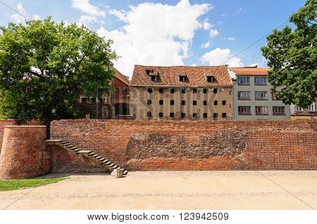 TORUN, POLAND - JULY 7, 2009: Rear view of an old granary and the West Gate from inside the moat between old and new towns