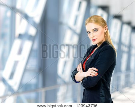Portrait of business woman. Photo with office building on background. Woman in red shirt and black suit.