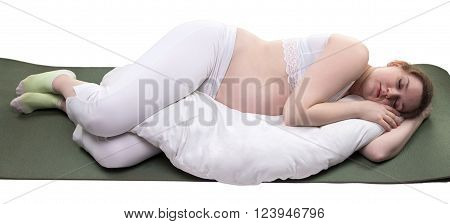 Pregnant sleeping woman and cushion on white background