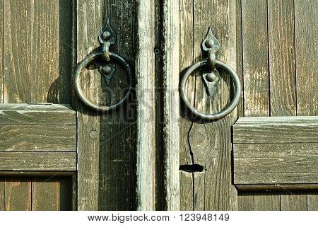 Wooden textured door with keyhole and worn iron door handles in the form of ring. Architectural detailed background. Vintage filter applied