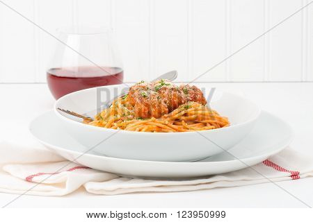 Plate of spaghetti and meatballs topped with fresh herbs and parmesan cheese.