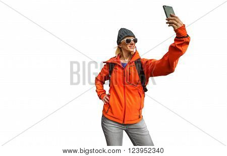 Smiling young sporty woman dressed jeans, orange wool windbreaker jacket and gray hat takes a selfie during a trekking. Isolated on white background.