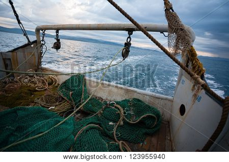 Fishing nets are on the deck of a small fishing vessel. Evening time.