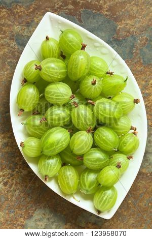 Raw gooseberries (lat. Ribes uva-crispa) on plate, photographed overhead on slate with natural light (Selective Focus, Focus on the gooseberries on the top)
