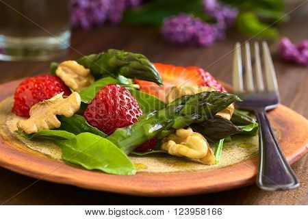 Fresh strawberry, green asparagus, baby spinach and walnut salad served on plate with fork, photographed on dark wood with natural light (Selective Focus, Focus on the asparagus head and the strawberry in the front)