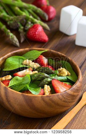 Fresh strawberry, green asparagus, baby spinach and walnut salad served in wooden bowl, photographed on dark wood with natural light (Selective Focus, Focus on the asparagus head in the middle of the bowl)