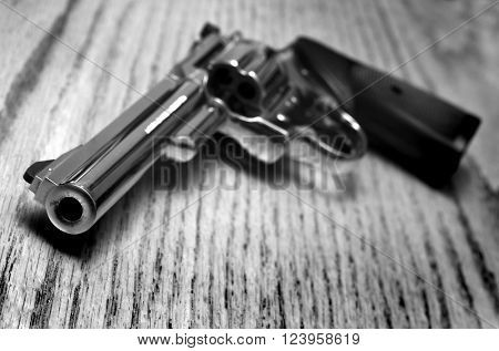 Closeup of powerful handgun with bullets on old wooden surface