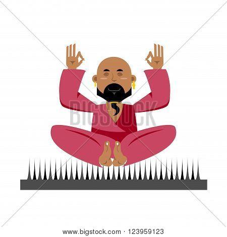 Yogi on nails. Indian yogi sits on spike. nirvana Meditation. Man practicing yoga exercises. Bald man with beard meditates