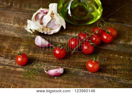 closeup of some cherry tomatoes, some garlic cloves and a glass cruet with olive oil on a rustic wooden table