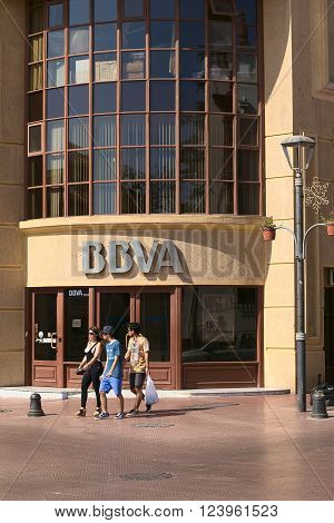 LA SERENA, CHILE - FEBRUARY 19, 2015: Unidentified people walking in front of a branch of the multinational Spanish banking group BBVA in the city center on February 19, 2015 in La Serena, Northern Chile. The bank building is situated on the corner of the