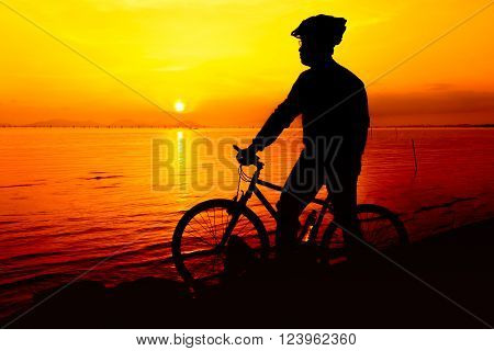 Silhouette of bicyclist enjoying the view at seaside, on colorful sunset orange sky background. Reflection of sun in water. Active outdoors lifestyle for healthy concept.