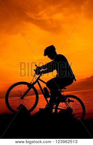 Silhouette of bicyclist riding the bike on a rocky trail at seaside, on colorful sunset orange sky background. Active outdoors lifestyle for healthy concept.