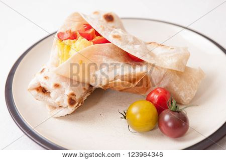 breakfast burrito with cheese eggs and heirloom cherry tomato