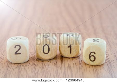 Number 2016 on wood dice on wooden background.