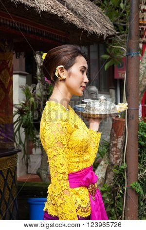 UBUD, INDONESIA - MARCH 2: Young woman with silver plate on the palm during the celebration before Nyepi (Balinese Day of Silence) on March 2, 2016 in Ubud, Indonesia.