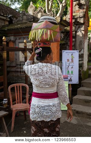 UBUD, INDONESIA - MARCH 2: Woman with basket on the head during the celebration before Nyepi (Balinese Day of Silence) on March 2, 2016 in Ubud, Indonesia.