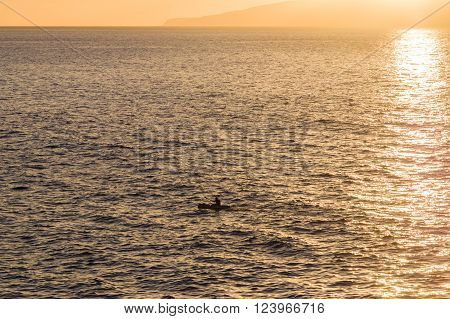 Silhouette of kayak oar in sunset light sun sparkles on water