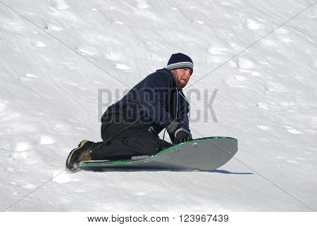 Man in toboggan on a sled on a snowhill going down laughing.