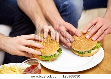 fast food, unhealthy eating, people and junk-food - close up of male hands with hamburgers and french fries on table at home