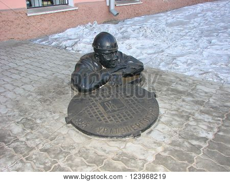 Yekaterinburg, Russia - February 27, 2012: Sculpture figure half man leaned out the hatch on his face - kindness and peace from the work done. On the hatch is written the name of the company and the year 1995. The sculptor is unknown. Sculpture plumbing.