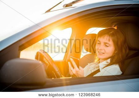 Young business woman driving car and looking simultaneously in her mobile phone