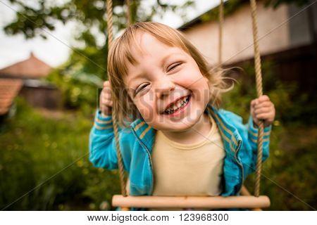 Joyous child swinging on seesaw in backyard
